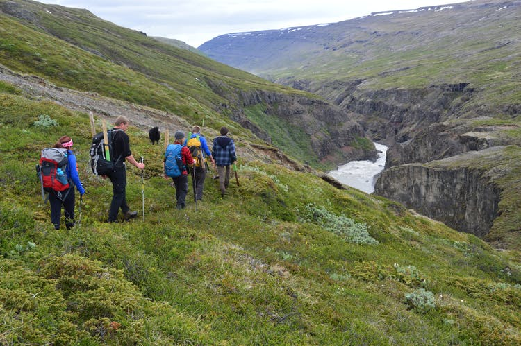 Hikers passing a river gorge in east Iceland.