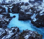 Beautiful blue Barnafoss, surrounded by snowy crags