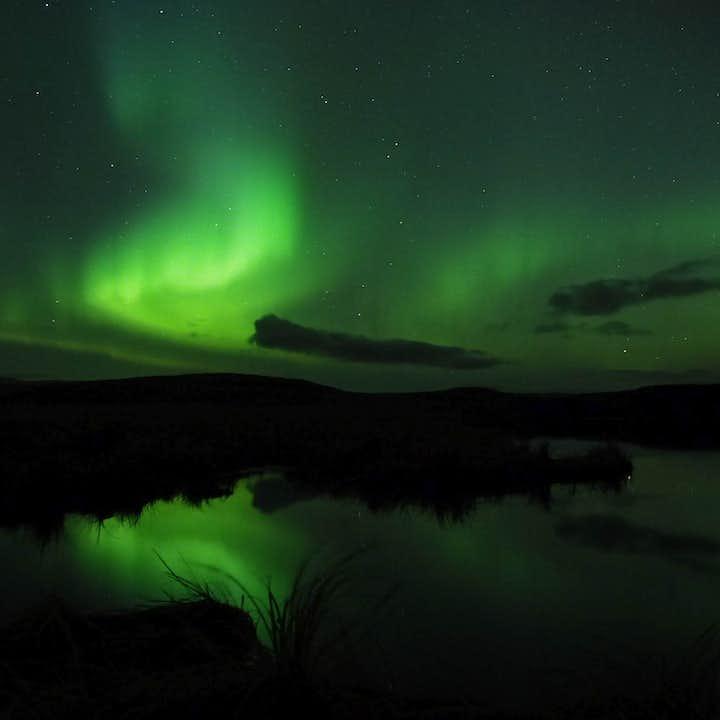 绝美的绿色北极光在河流上方现身