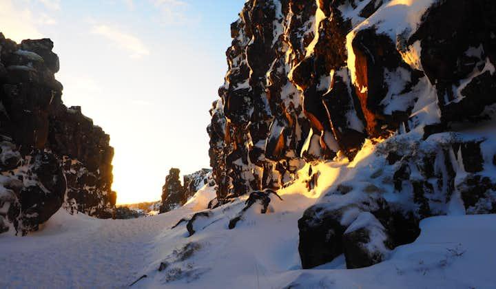 Sun beams down on snowy rock formations in a gorge in Þingvellir