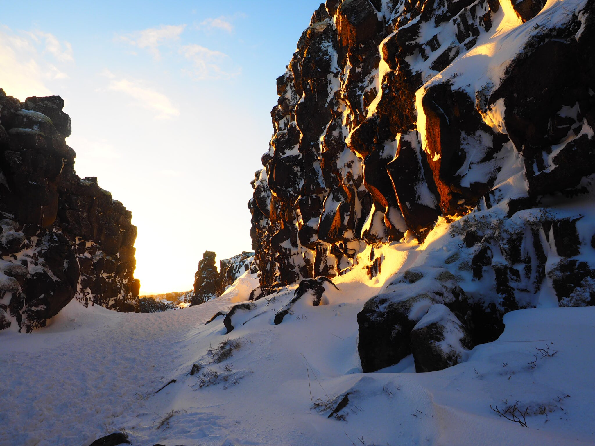 Sun beams down on snowy rock formations in a gorge in Þingvellir