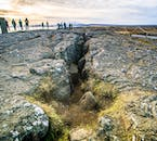 Visitors explore a tectonic crack on a sunny day in Þingvellir national park