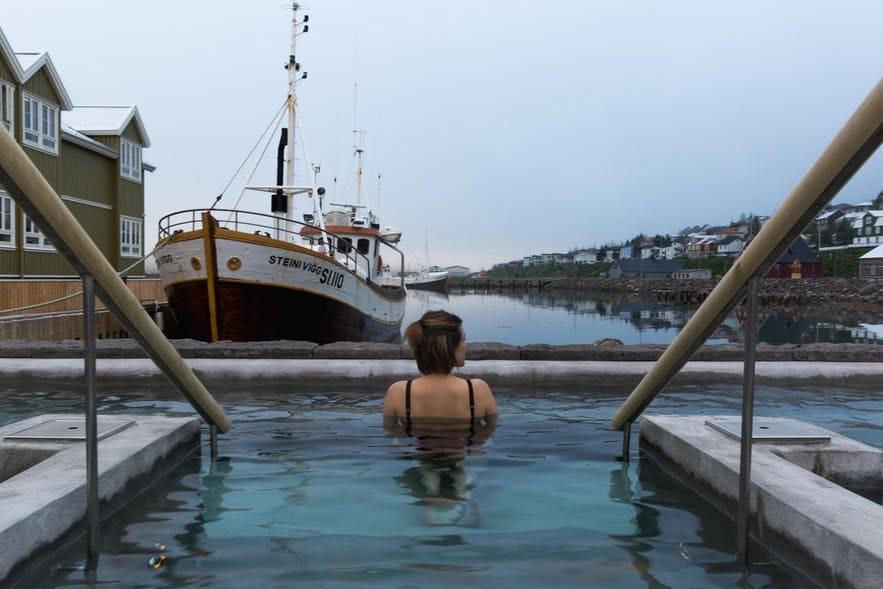 在冰岛锡格吕菲厄泽的温泉泳池中放松身心,体验冰岛峡湾小镇的避世风情