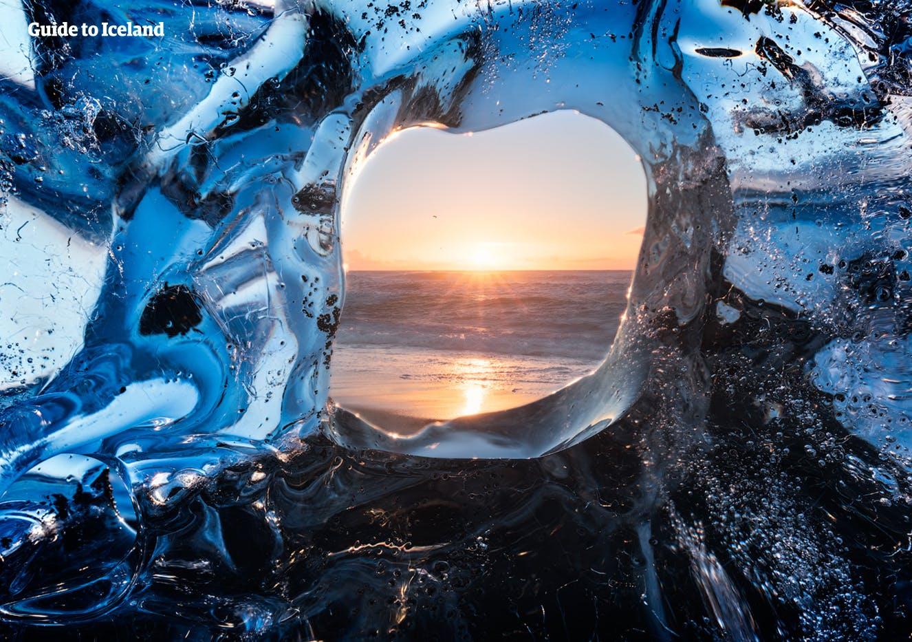 从一块躺在钻石沙滩上的碎冰之间观看冰岛杰古沙龙冰河湖的景色。