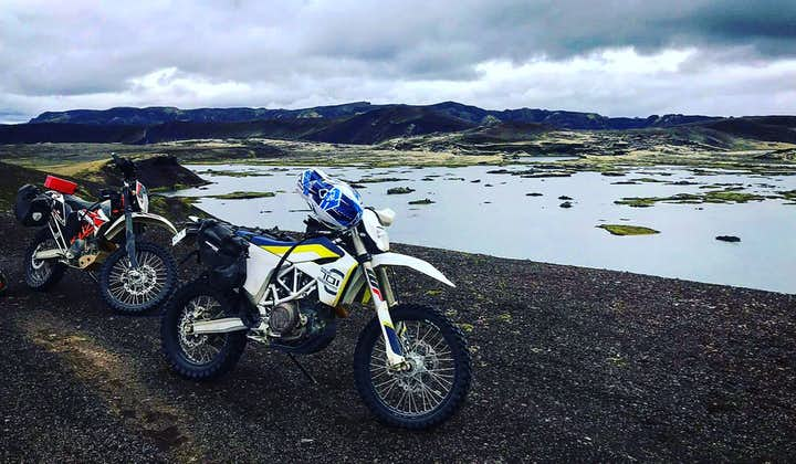 A husky motorcycle resting at a highland lake with moss covered mountains in the background.
