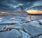 Kirkjufell mountain on Snæfellsnes peninsula, covered in ice, overlooking the Grundafjörður fjord.
