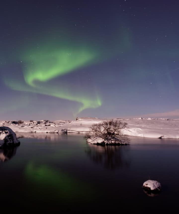 Des aurores boréales brillent sur le lac près d'Akureyri.
