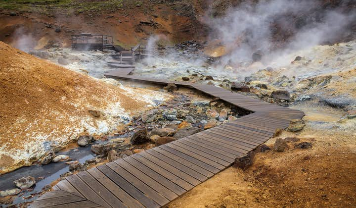 Steam rises from the ground amid wooden walkways in the Seltún geothermal area