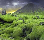 Bright green moss covers the rocks at the foot of an imposing mountain