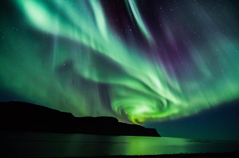 Spektakularna zielona zorza polarna nad jeziorem w Islandii