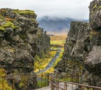 Travellers walk along a path near the main tectonic rift in Þingvellir