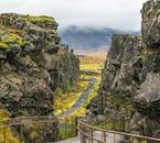 Travellers walk along a path near the main tectonic rift in Þingvellir
