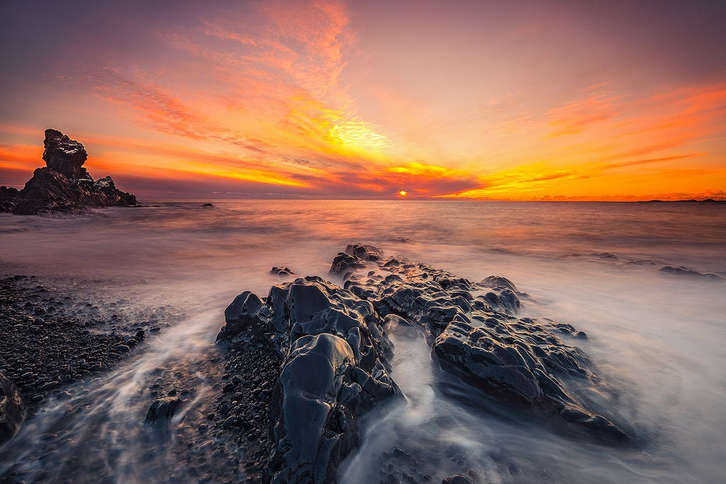 Shades of pink and orange fill the sky as the sun sets over the dramatic coastline of the Snæfellsnes peninsula.