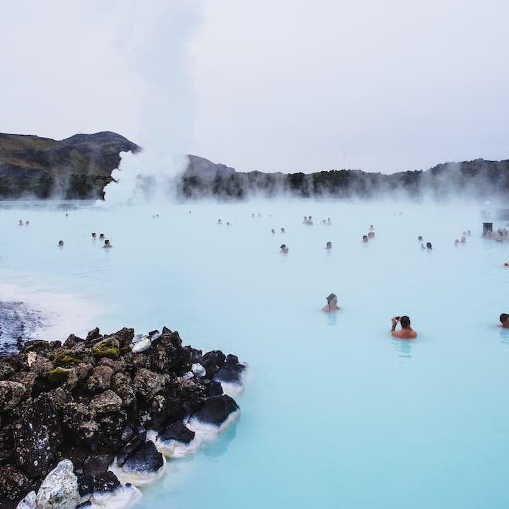 Visitors enjoying the healing properties of the Blue Lagoon in summer.