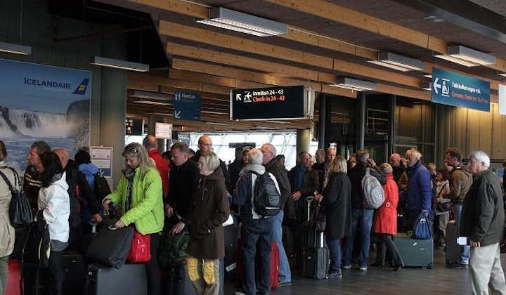 Dei viaggiatori mentre aspettano il check-in nella hall delle partenze.