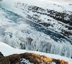 Gullfoss waterfall in winter, half bound in Ice.