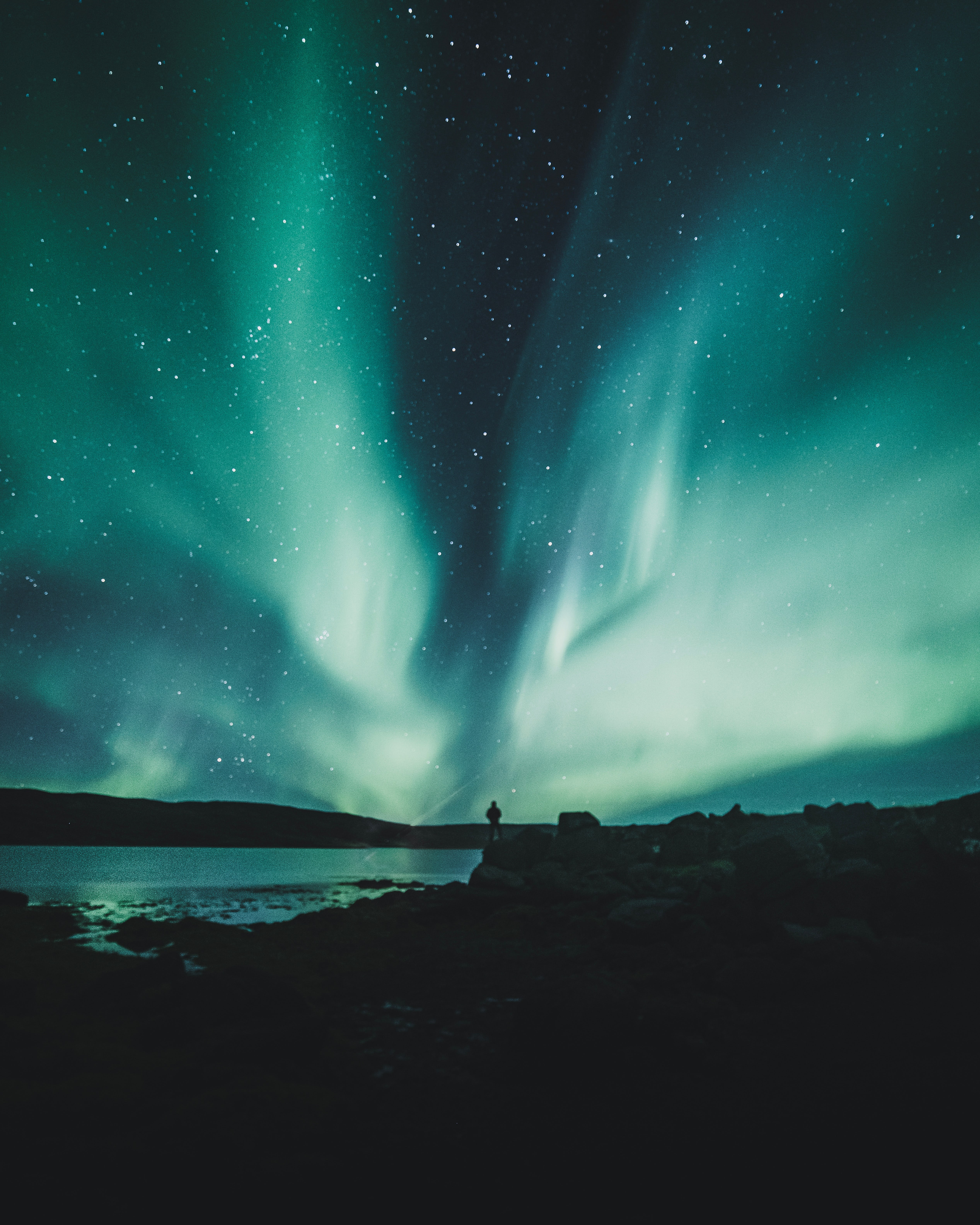 A phenominal display of whitish green northern lights dancing over the fjords of west Iceland.