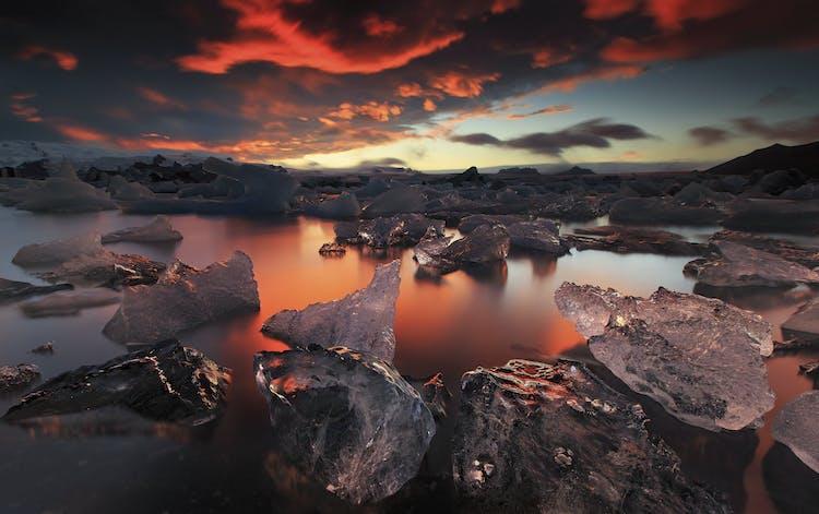 Ледниковая лауна Йокульсарлон на закате, ледяные осколки отражают золотистые лучи полуночного солнца.