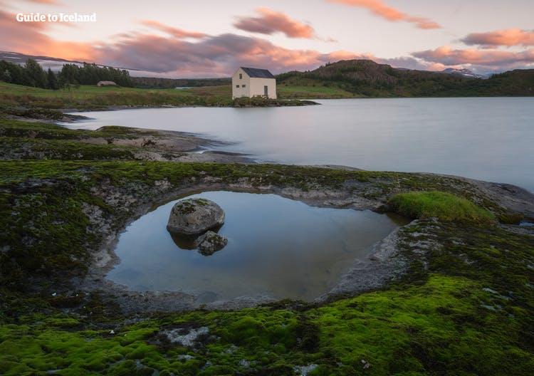 Ein altes Haus am Ufer des Flusses Lagarfljót im Osten Islands an einem ruhigen Sommerabend.