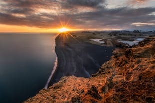 The sun sets over the endless black sands of Iceland's South Coast.