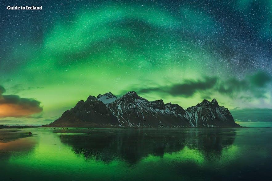 Zorza polarna na Islandii odbijająca się w wodzie.