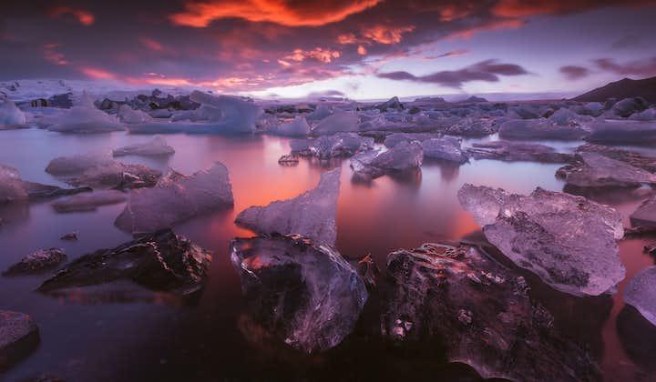 Glittering icebergs serenely drifting on Jökulsárlón glacier lagoon at sunset.