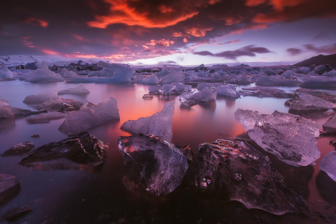 Icebergs scintillants dérivant sereinement sur la lagune du glacier de Jökulsárlón au coucher du soleil.