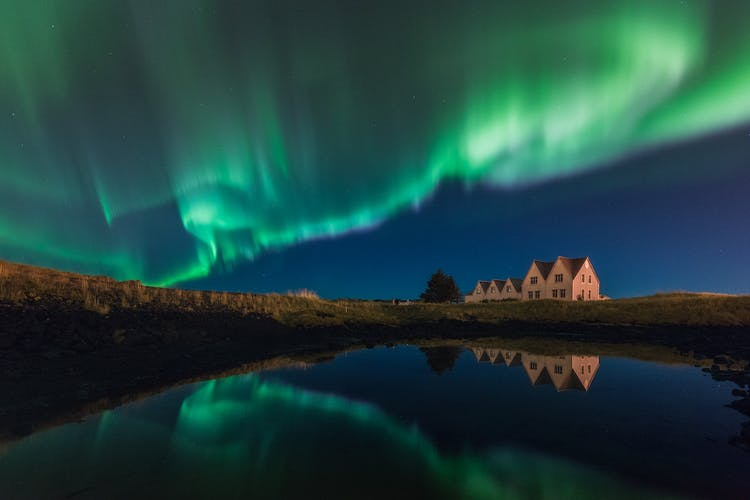 Northern Lights dance over the mountains of Iceland. Make sure to return to Iceland soon.