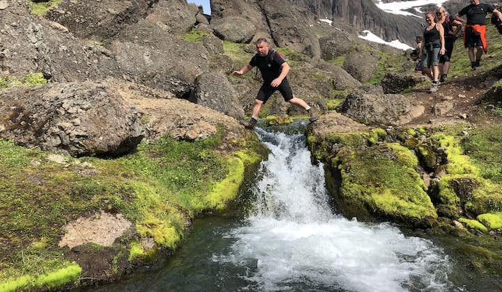 A man jumping over a brook in the east highlands, near Borgarfjörður eystri, iceland.