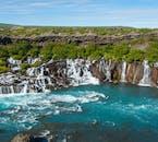 Hraunfossar cae en un día brillante, brotando de la lava y el acantilado cubierto de tierra.