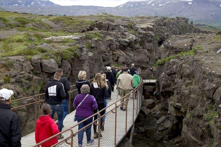 People walking on the elevated bridges in Þingvellir over the massive tectonic rifts.