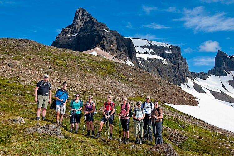 Hikers reaching the high peaks above the fjords on a summers day.