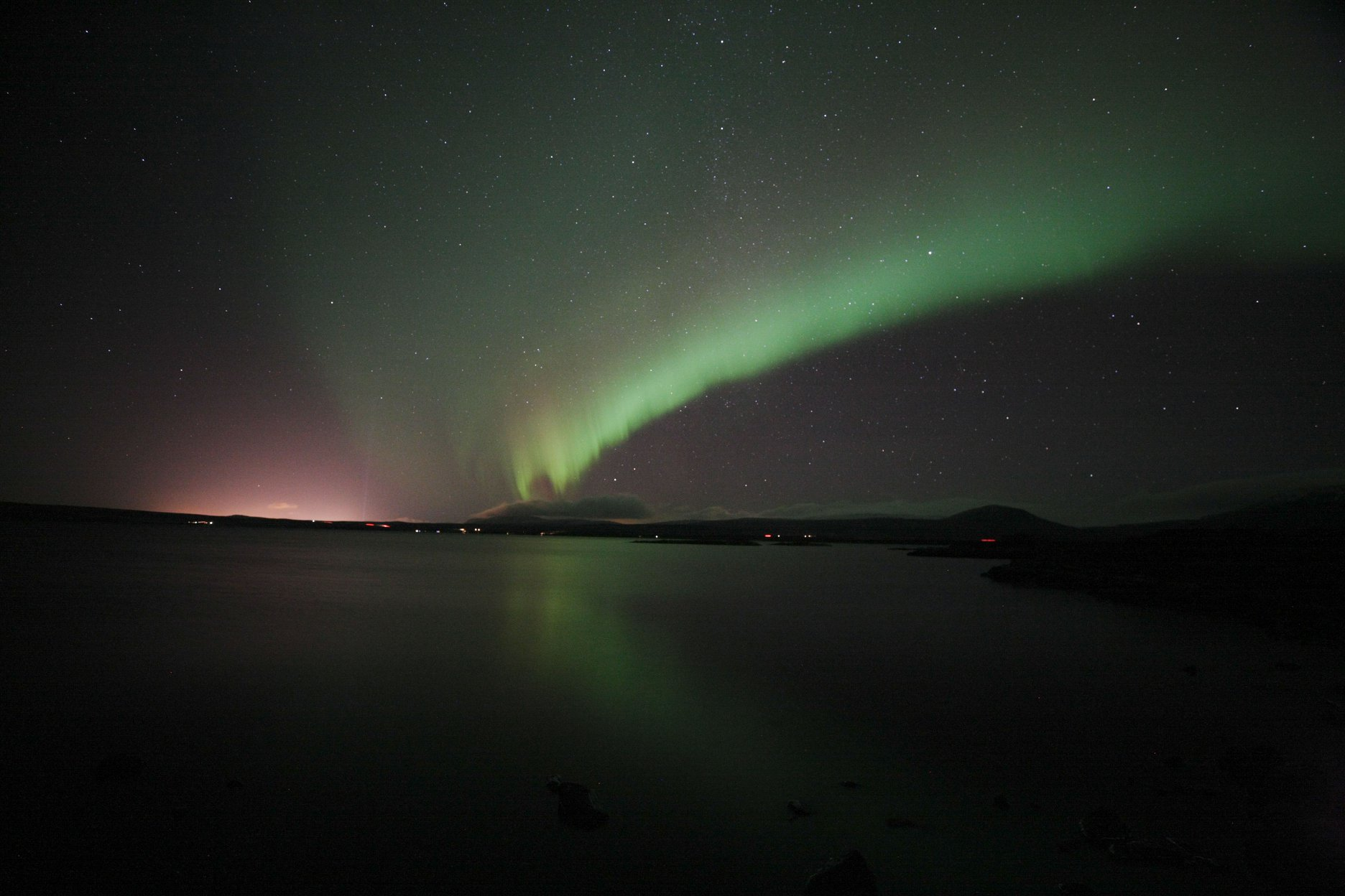 A blaze of green and pink northern lights forming int he sky.
