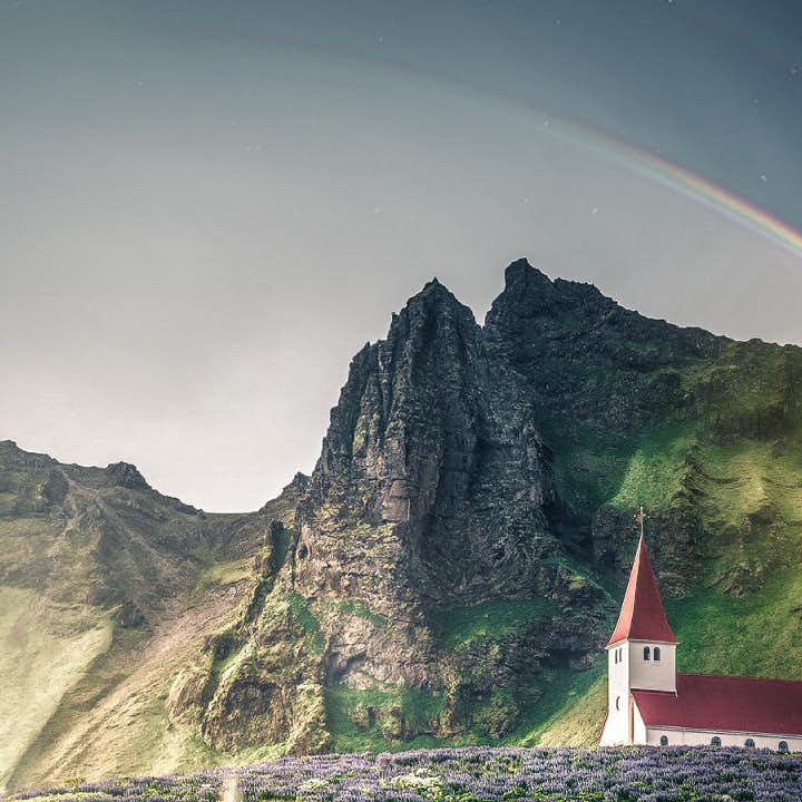 A rainbow shines over the picturesque church in Vík.