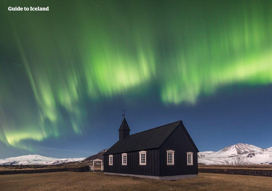 A windswept church under the northern lights, before Snæfellsjökull glacier.