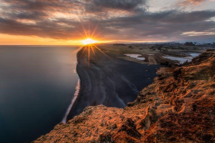 Die Mitternachtssonne berührt den schwarzen Sand an Islands Südküste.