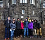 A happy tour group stands in front of the parliament building in Reykjavík.