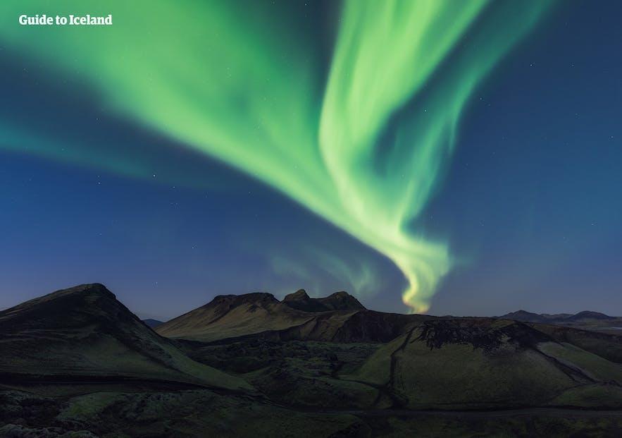 Las auroras arremolinándose sobre un paisaje montañoso en Islandia.