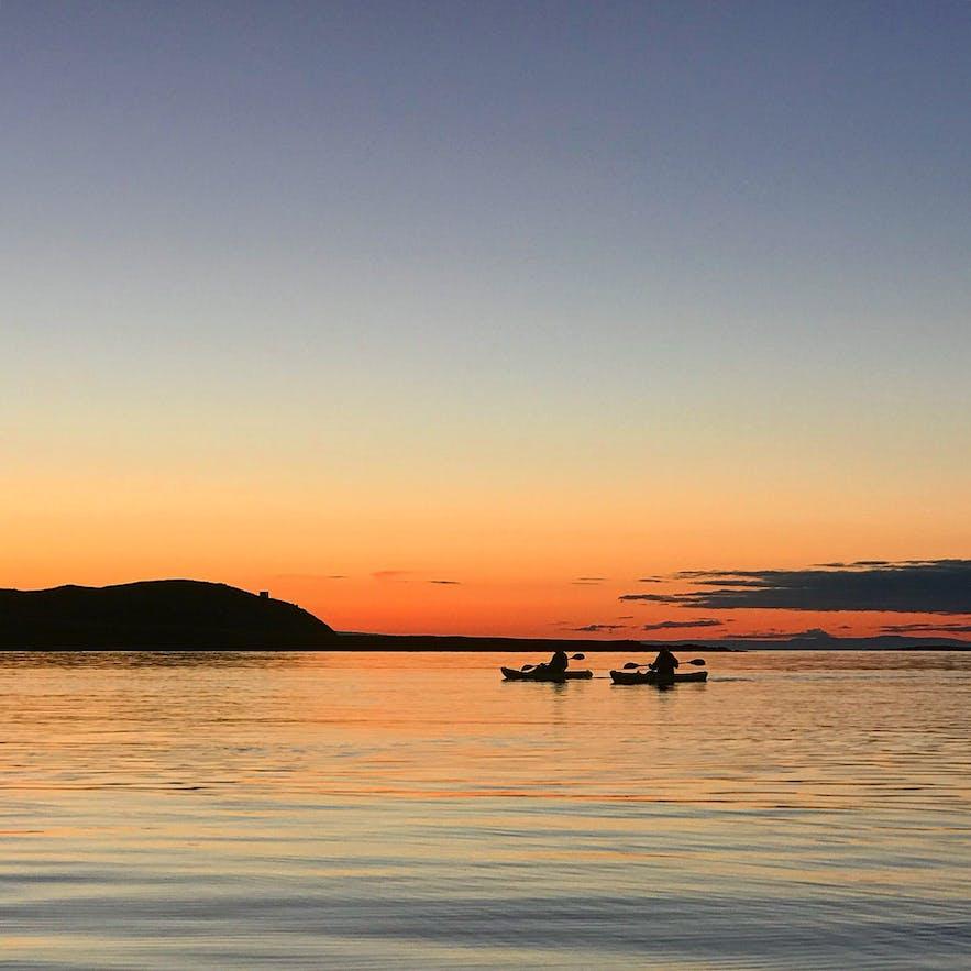 乘皮划艇游弋于午夜阳光照耀下的美丽海面