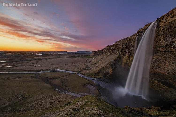 The midnight sun illuminating the sky above Seljalandsfoss waterfall on the South Coast.