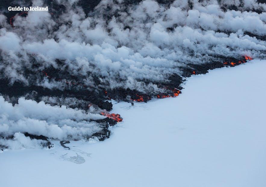 Kontrast erupcji wulkanu z białym śniegiem.