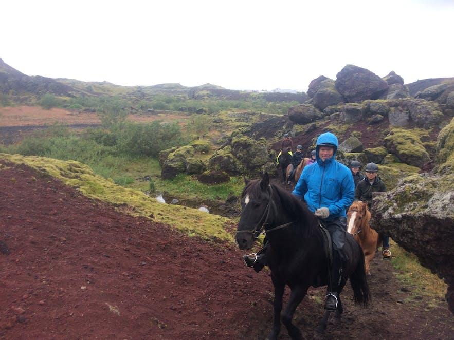 溶岩景観のなかを進む乗馬体験のグループ