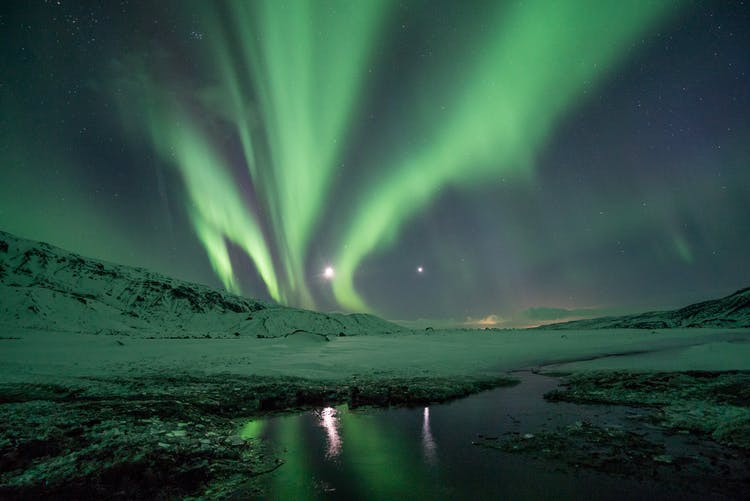 Green ribbons of the Northern Lights flying across a fjord in East Iceland.