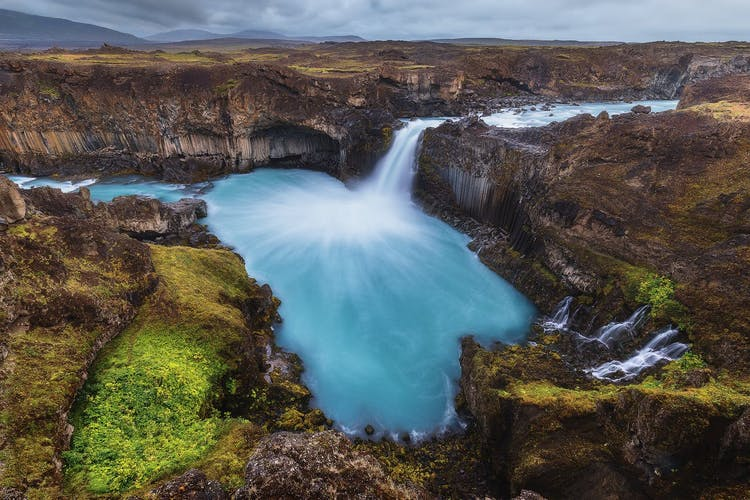 Goðafoss waterfall in summer, with a rainbow arching from it, pictured in north Iceland.
