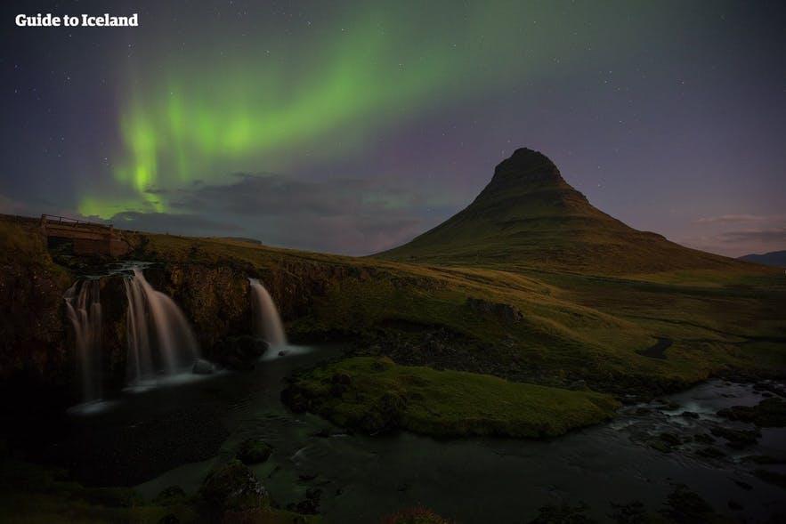 Kirkjufellsfoss and Kirkjufell in west Iceland, beneath the magical Northern Lights.