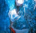 Światło przeszywa szkliste ściany jaskini lodowej na Islandii.