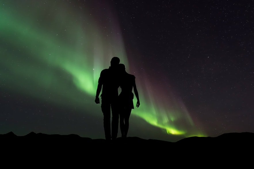 A young couple look to the Northern Lights.