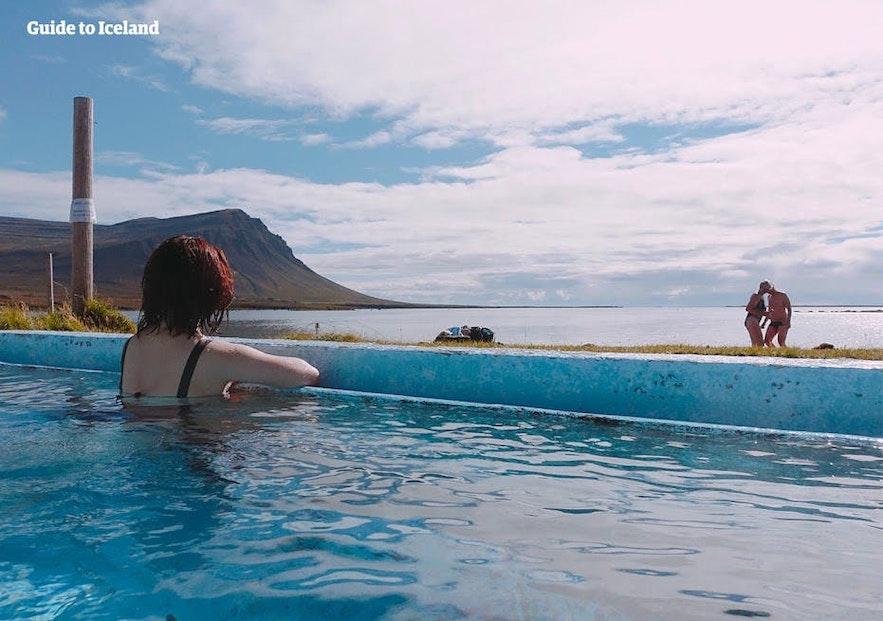 Une femme regarde les vues de sa piscine extérieure.