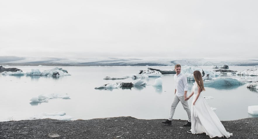 Honeymooners walk beside a glacier lagoon in South Iceland.