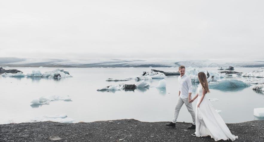 Les jeunes mariés marchent à côté d'une lagune glaciaire dans le sud de l'Islande.